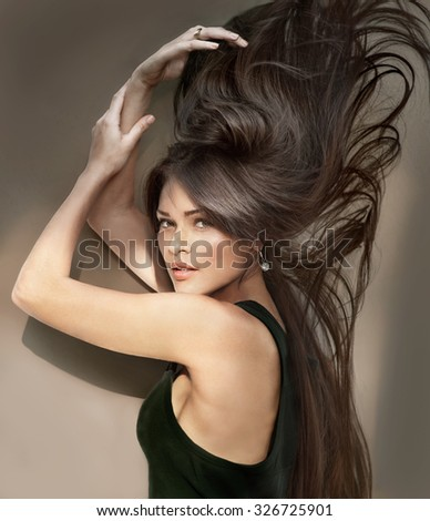 Portrait of beautiful young woman with long hair in motion. Shooting outdoors - stock photo