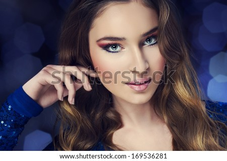 Portrait of beautiful young woman with long wavy hair and nice make up. Fashion