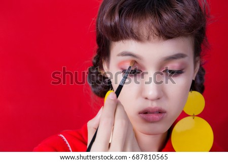 Portrait of beautiful young woman with make-up on her eye lid on red background.