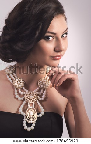 Portrait of beautiful young woman with makeup with golden jewelry - stock photo