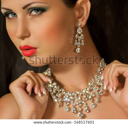 Portrait of beautiful young woman with makeup with jewelry precious decorations. - stock photo