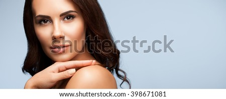 portrait of beautiful young woman with naked shoulders, on grey background, with blank copyspace area for slogan or text message - stock photo