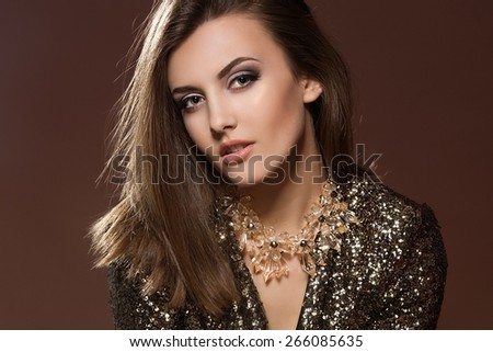 Portrait of Beautiful young woman with necklace and in gold jacket. Fashion and beauty. Gold make up. - stock photo