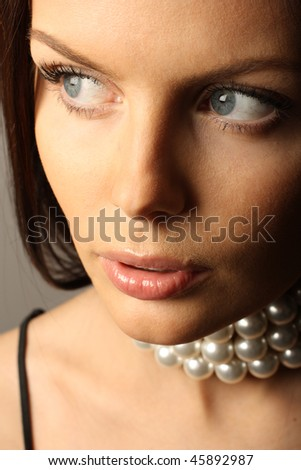 Portrait of beautiful young woman with pearls - stock photo