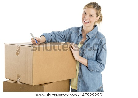 Portrait of beautiful young woman with pen standing by stacked cardboard boxes against white background