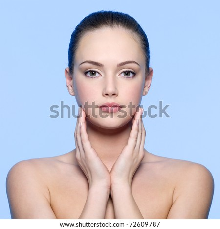 Portrait of beautiful young woman with  perfect  skin - blue background