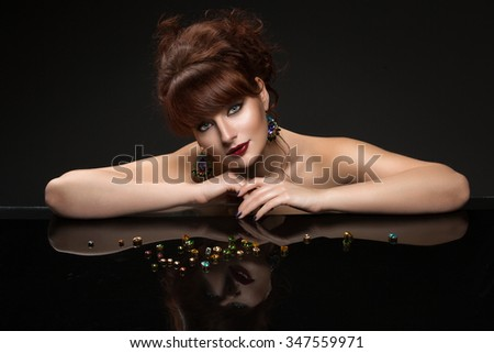 Portrait of beautiful young woman with red hair and bright makeup leaning on glass table. Crystal earrings. Over dark background. - stock photo