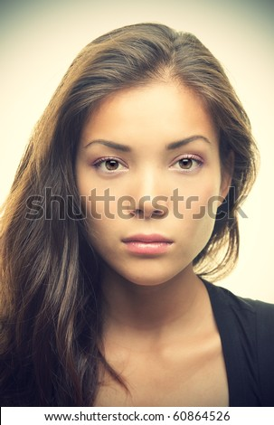 Portrait of beautiful young woman with serious look. Mixed race Asian Chinese / White Caucasian female model.