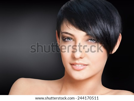 Portrait of beautiful young woman with short hairstyle on black background - stock photo