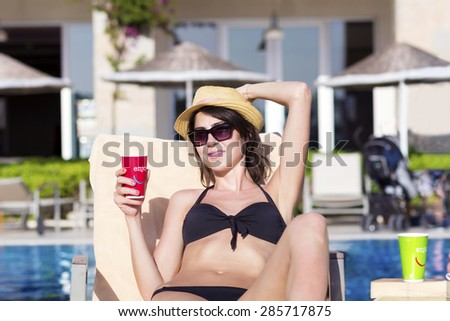 Portrait of beautiful young woman with straw hat drinking juice on the pool.Summer vacation - stock photo