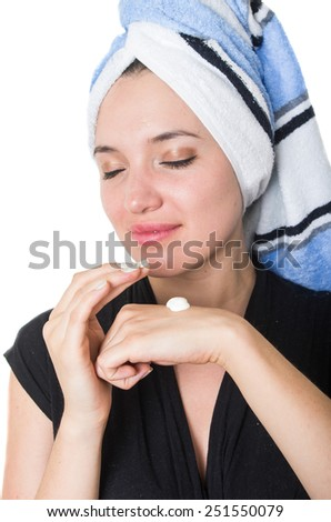 portrait of beautiful young woman with towel tied around her hair applying cleaning cream moisturizer to her face isolated on white - stock photo