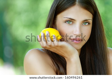 Portrait of beautiful young woman with yellow lemon, against background of summer green park. - stock photo