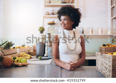 Portrait of beautiful young woman working at juice bar, she is standing behind counter looking away and smiling. - stock photo
