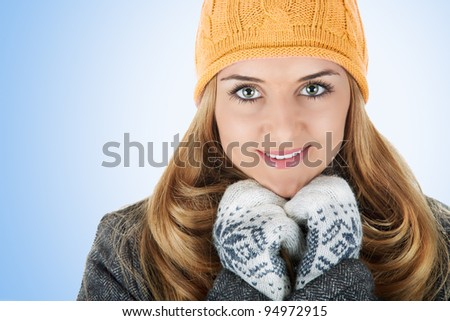Portrait of beautiful young women in winter clothes over light blue background. - stock photo