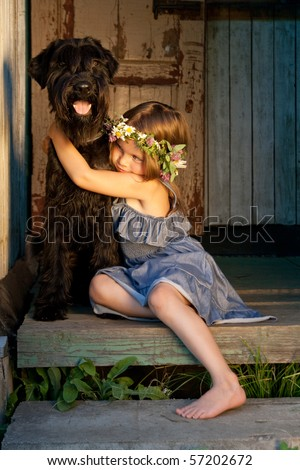 Portrait of beautifull girl and her black dog at the sunlight. - stock photo