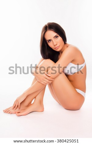 portrait of beautifyl young woman  in underwear huging her legs - stock photo