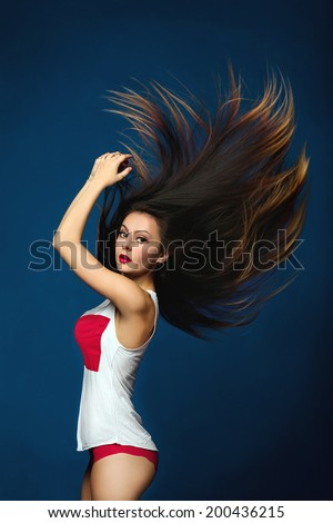 Portrait of beauty attractive fashion slim healthy young woman with fluttering hair and perfect training sexy tanned skin sport body in an ideal white and red lingerie isolated on dark blue background - stock photo