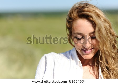 portrait of beauty blonde woman stay on green field