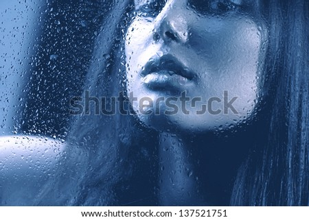 Portrait of Beauty Girl behind the Wet Glass. Melancholy Woman. Rain. Beautiful Model Looking Through the Window with Rain Drops - stock photo