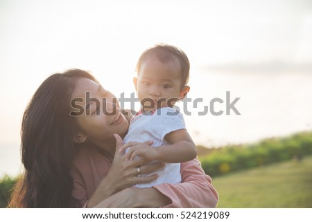 portrait of Beauty Mother and her Child playing in Park together