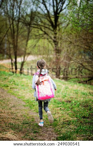 Portrait of beauty pre-teen tween kid girl with long brunette hair wearing pink rucksack and walking in the park after school on warm spring day