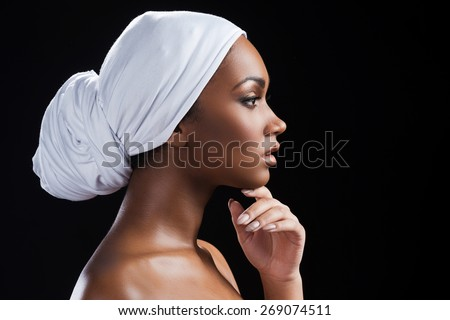 Portrait of beauty. Side view of beautiful African woman wearing a headscarf and holding hand on chin while standing against black background