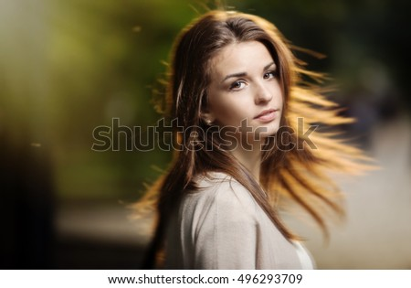 Portrait of beauty woman with perfect smile walking on the street and looking at camera, sunset light