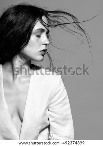 Portrait of beauty young brunette woman portrait in white fashion female jacket on gray background