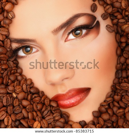 portrait of beauty young female face drowning in coffee beans with beautiful brown make-up