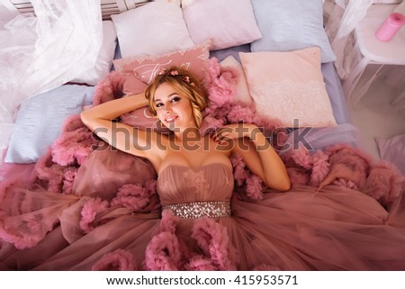 Portrait of beauty young woman in pink dress, lying - stock photo