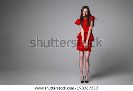 Portrait of beautyful posing  woman with long  hair in red dress, studio shot - stock photo