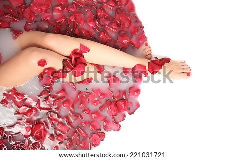 portrait of beautyfull hot pinup girl, red hair taking relaxing bath with flower petals on white copy space background , outdoor - stock photo