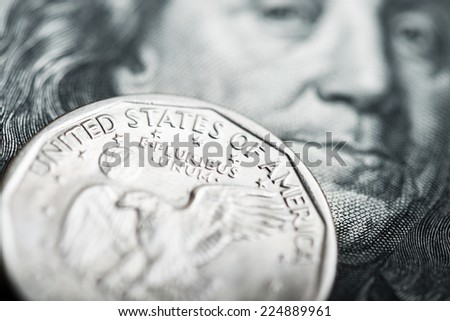 Portrait of Benjamin Franklin from one hundred dollars banknote and one dollar coin  - stock photo