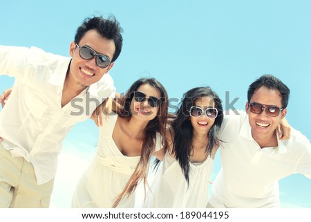 Portrait of best friend in white having fun laughing together at the beach - stock photo