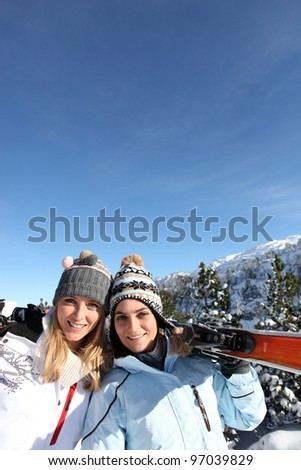 portrait of best friends at ski resort against deep blue sky background - stock photo