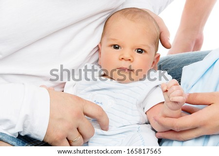 Portrait of bewborn baby boy surrounded by mother and father's hands