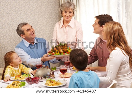Portrait of big family at festive table looking at aged female with dish of delicious turkey - stock photo