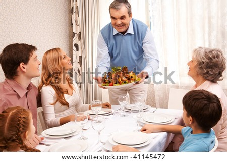 Portrait of big family sitting at festive table and looking at aged man with cooked turkey - stock photo