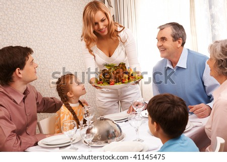 Portrait of big family sitting at festive table and looking at pretty female with dish of delicious turkey - stock photo