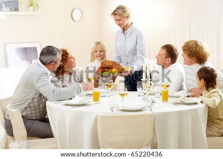 Portrait of big family sitting at festive table and looking at pretty woman with roasted turkey - stock photo