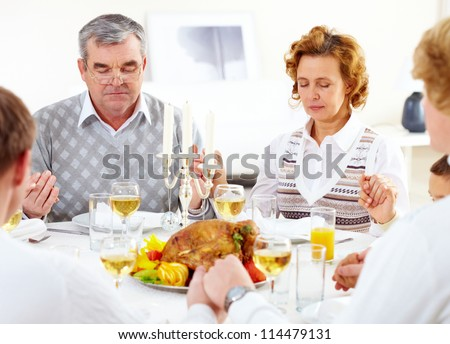 Portrait of big family sitting at festive table and praying before dinner - stock photo