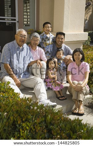 Portrait of big family sitting on front steps of house - stock photo