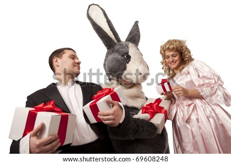 Portrait of big grey fur's color rabbit giving present to a pretty girl in pink dress and Gentleman with gift boxes. Isolated over white background - stock photo