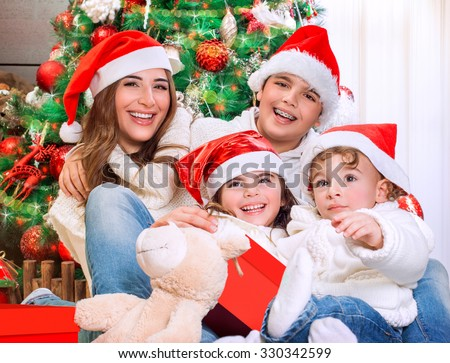 Portrait of big happy family in Xmas eve sitting under festive decorated Christmas tree, celebrating holidays at home - stock photo