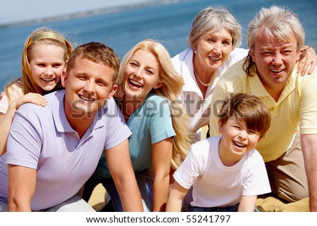 Portrait of big happy family looking at camera during vacation - stock photo