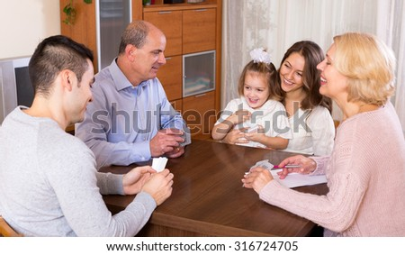 Portrait of big multigenerational family playing cards - stock photo