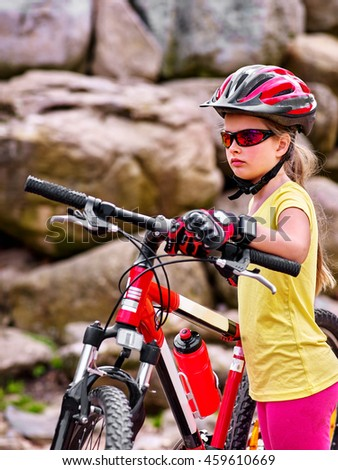 Portrait of bikes girl in bicyclist glasses. Girl rides bicycle into mountains. Girl wearing helmet and gloves on bicycle in mountaineering . Mountaineering is good for health. Summer outdoor.