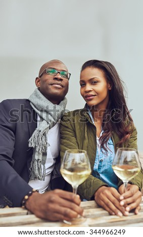 Portrait of black couple dating, sitting on a coffee shop outside - stock photo
