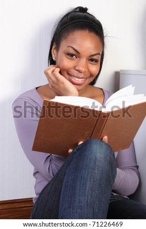 Portrait of black girl wearing jeans and purple top, sitting on floor at home, reading a book. Girl is sitting with her back to the wall and is looking up with a happy smile. - stock photo