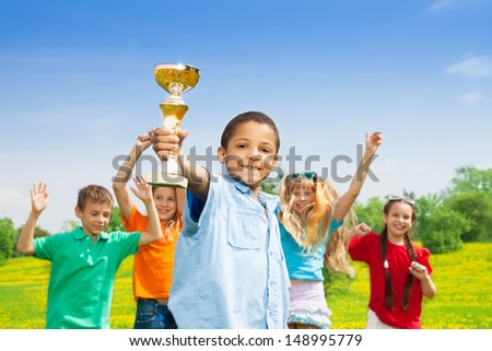 Portrait of black happy smiling little boy holding prize cup with his team on background - stock photo